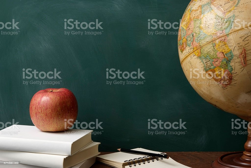 Red apple on stacked blank books with globe against blackboard stock photo