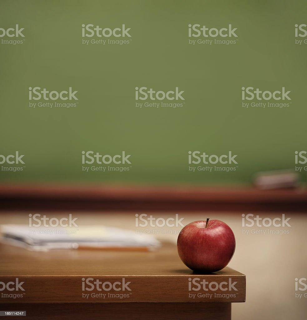 Red apple on teacher's desk. stock photo