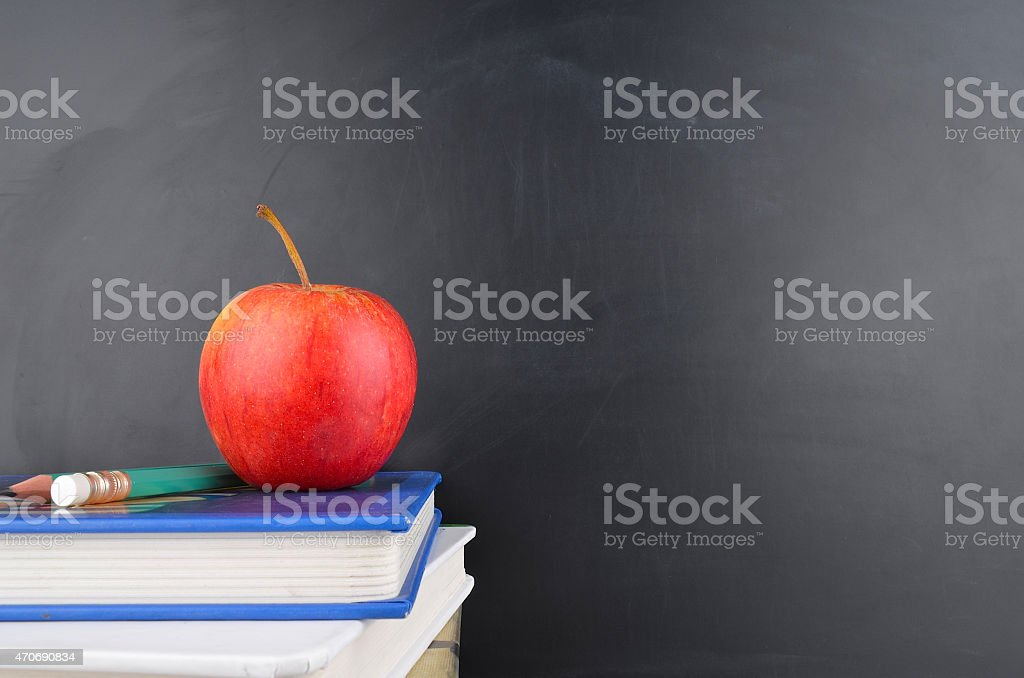 A red apple on top of books in front of a chalkboard stock photo