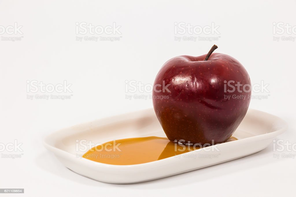 Red apple on white plate with honey stock photo