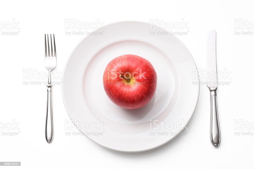 Red apple on white plate with silverware on white background stock photo
