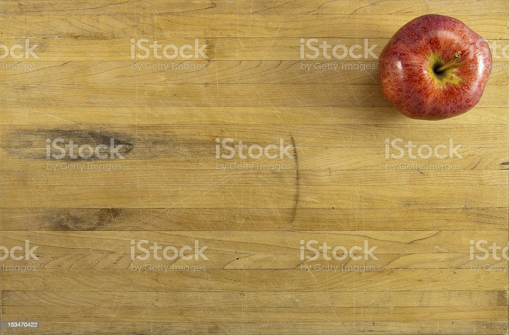 Red Apple on Worn Cutting Board royalty-free stock photo
