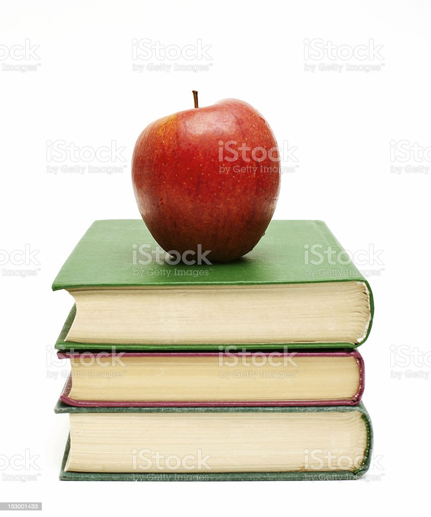 A red apple sitting on a stack of textbooks stock photo