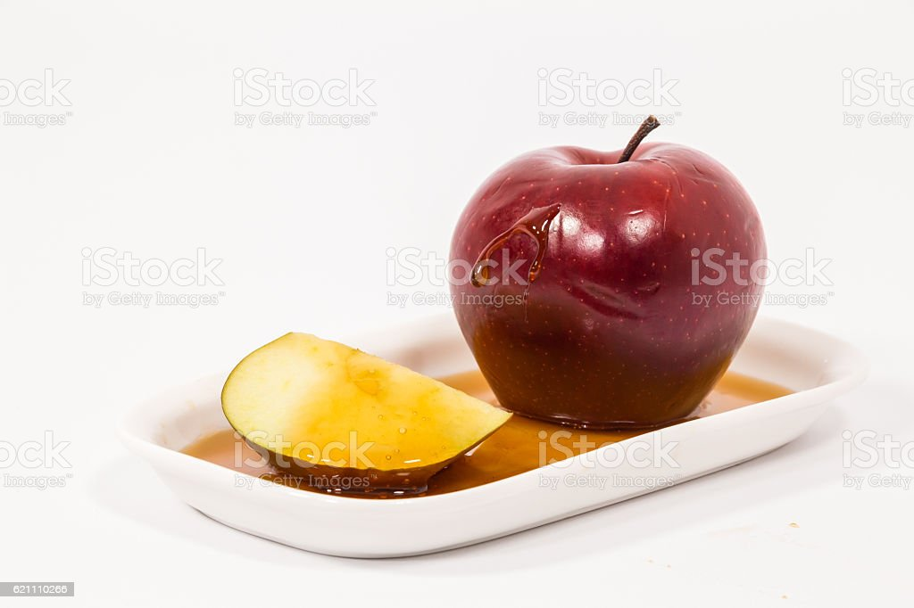 Red apple slice with drops of honey on plate stock photo