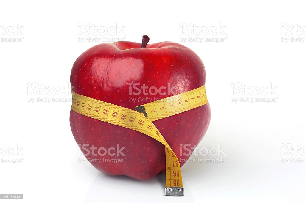 Red apple squeezed by tape measure royalty-free stock photo