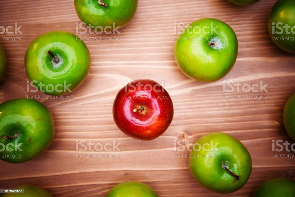 Red apple standing out from the crowd of green apples royalty-free stock photo