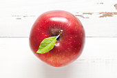 Red apple with leaf on white table