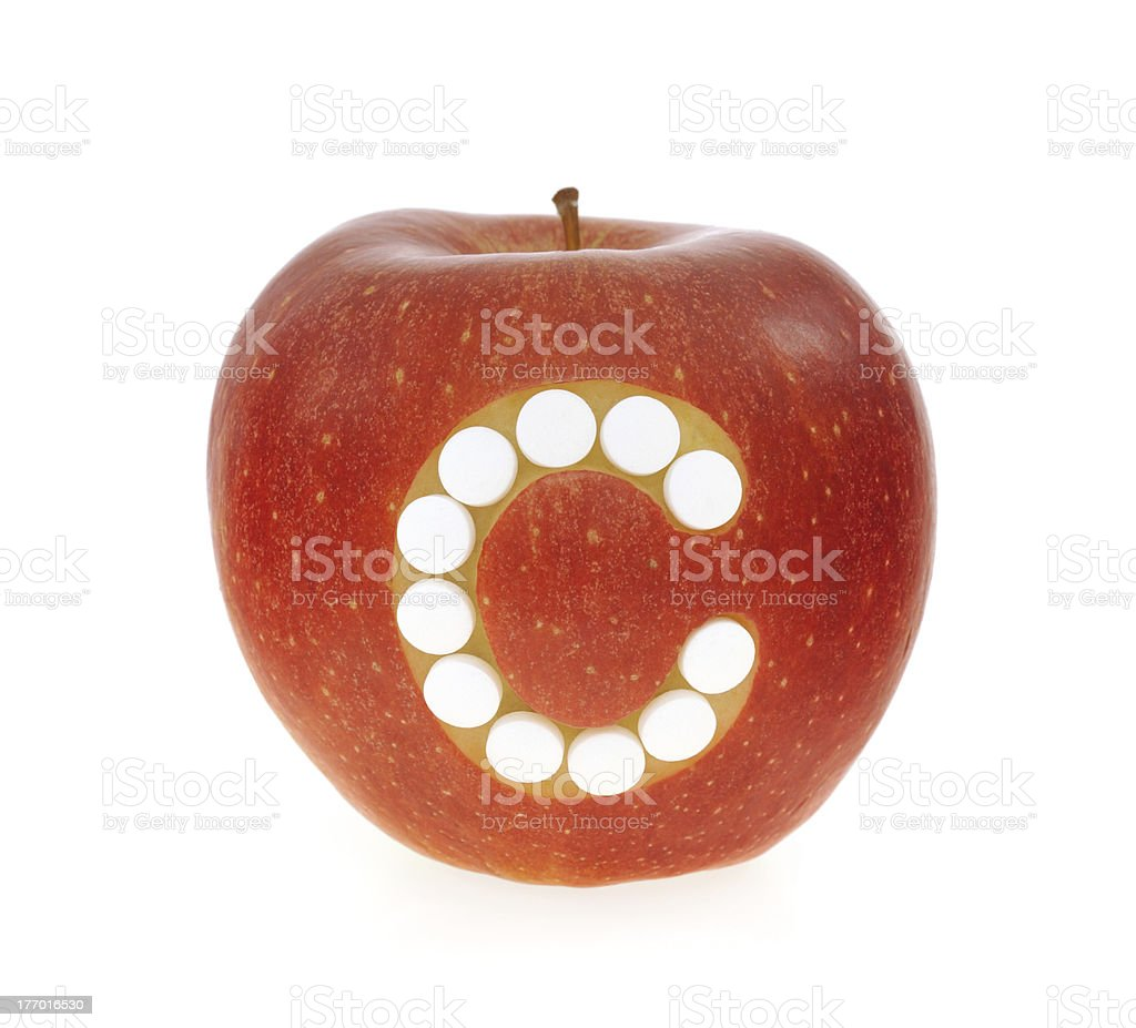 Red apple with vitamin c pills over white background royalty-free stock photo