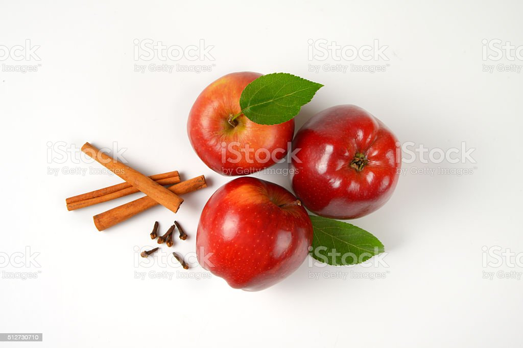 red apples, cinnamon sticks and dried cloves stock photo