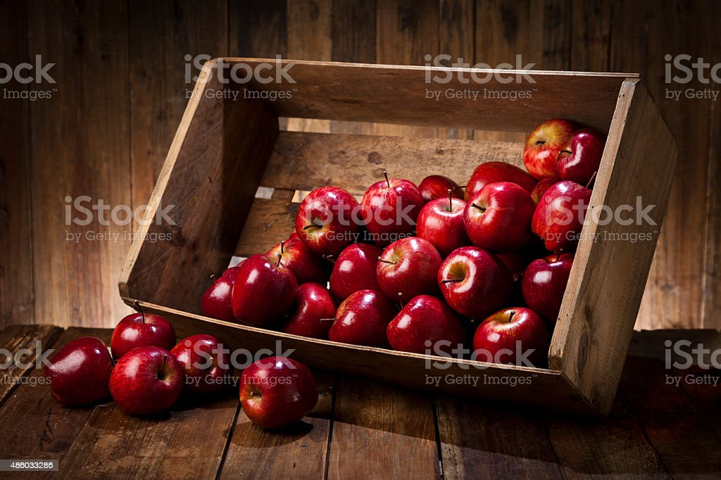 Red apples in a crate on rustic wood table stock photo