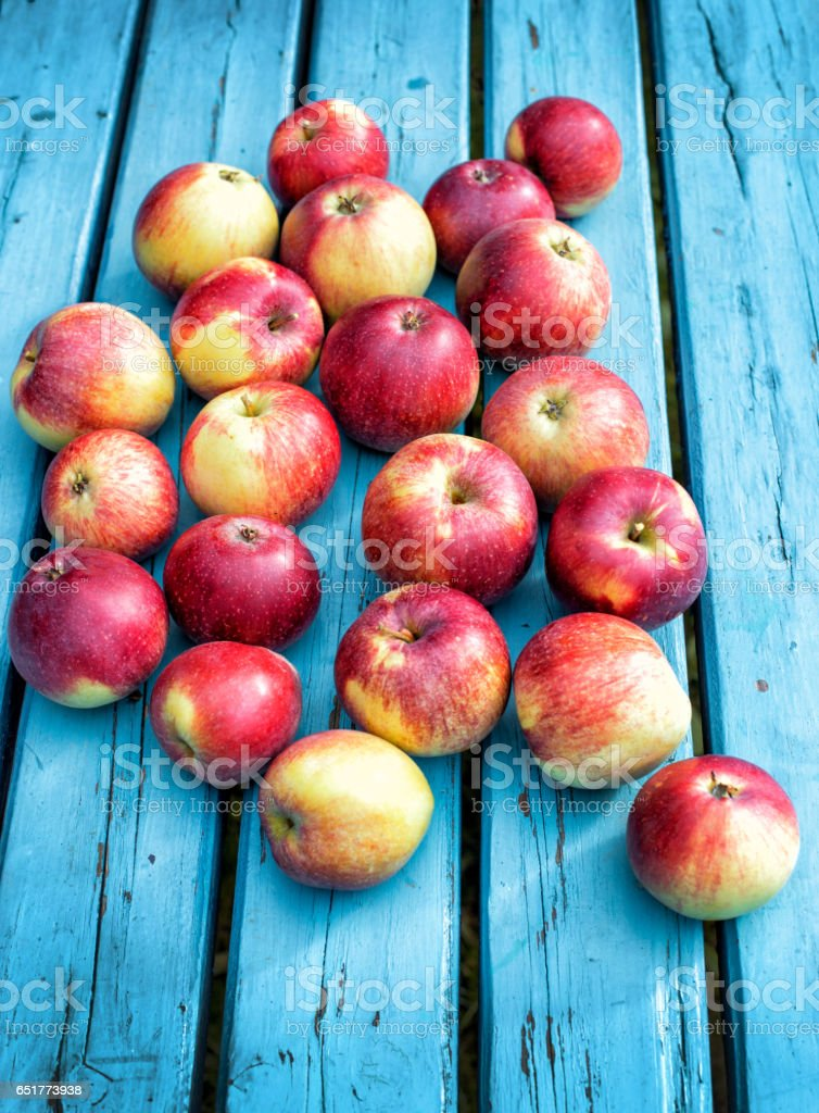 Red apples lie on a blue plank stock photo