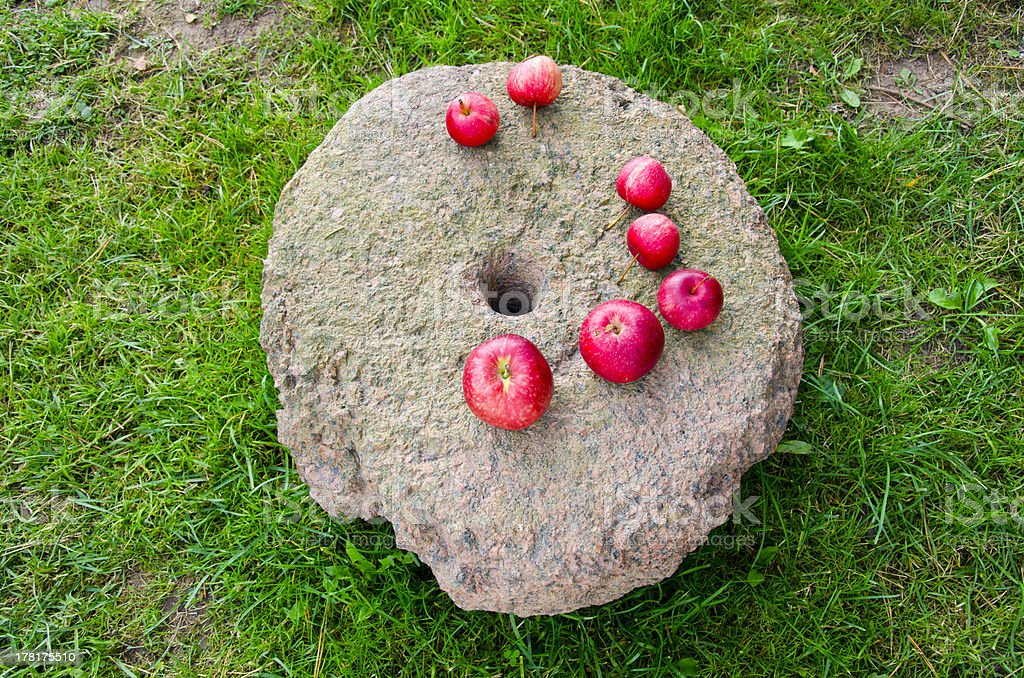 red apples on ancient millstone stock photo