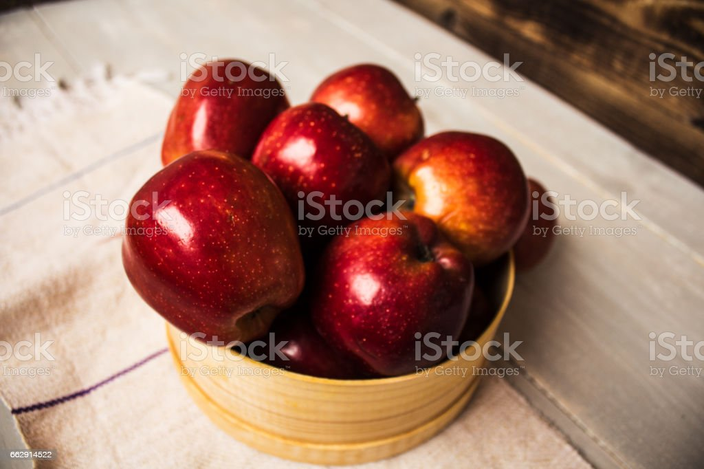 red apples on in wooden bowl stock photo