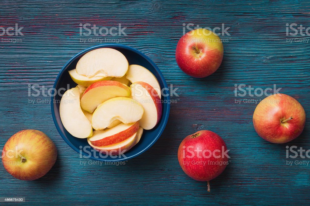Red apples with slices over blue wooden background stock photo