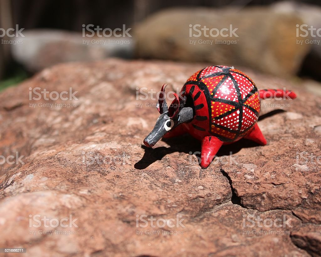 Red armadillo bobble head toy on a rock stock photo
