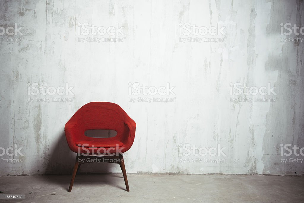 red armchair near the wall stock photo