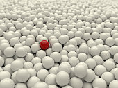 A red ball in a pile of white balls