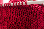 Red ball of yarn with needles close-up