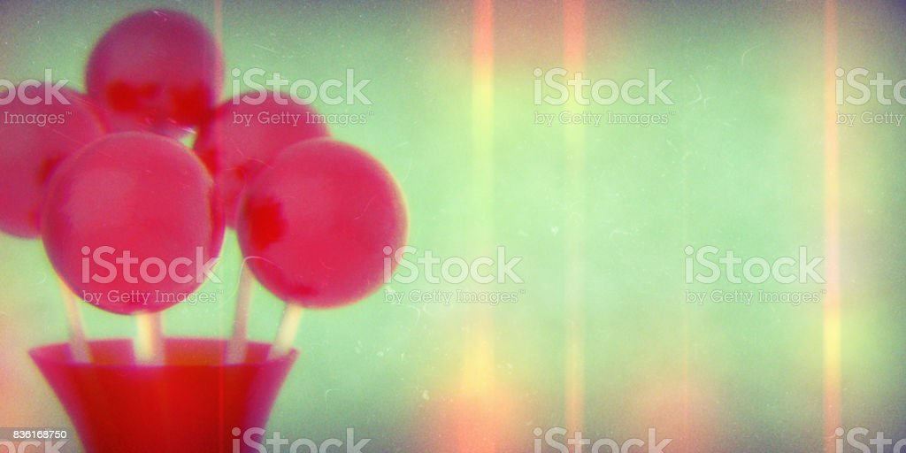 Red balls of lollipops on stick in red vase on retro background with shallow DOF stock photo