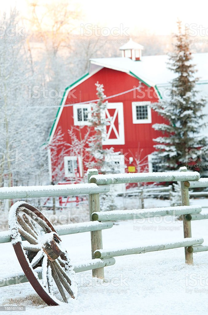 Red Barn and Wagon Wheel in Winter stock photo