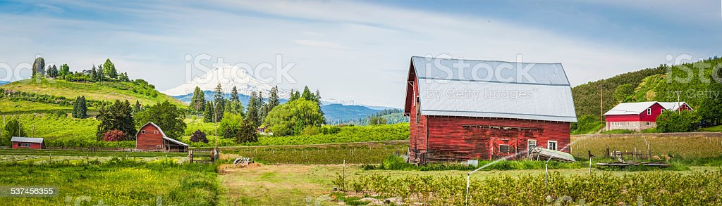 Red barn green farm agricultural landscape white mountain peak panorama stock photo
