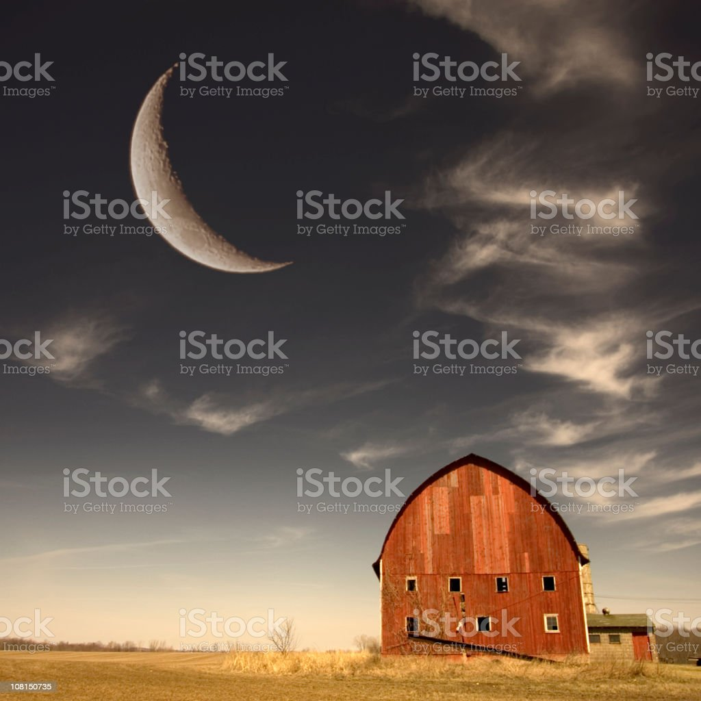 Red Barn in Field with Large Crescent Moon at Dusk royalty-free stock photo