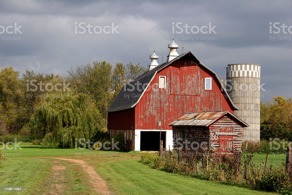 Red barn in Minnesota with a dark cloudy sky behind it royalty-free stock photo