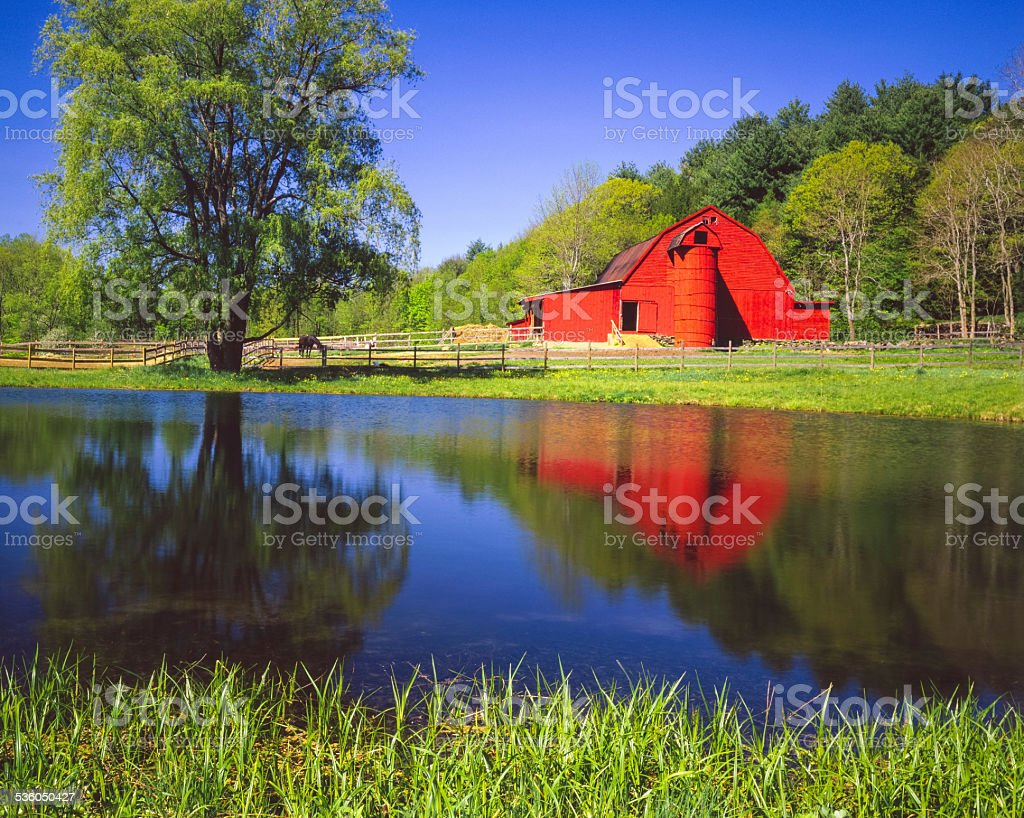 Red barn reflection with pond in Vermont New England,USA stock photo