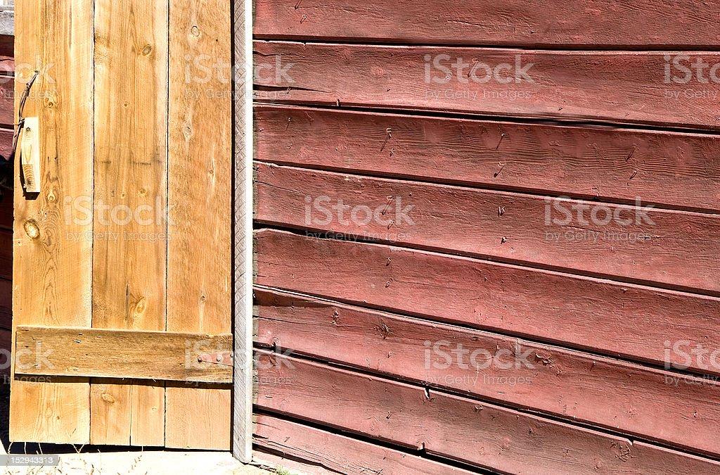 Red Barn Siding with Raw Wood Door stock photo