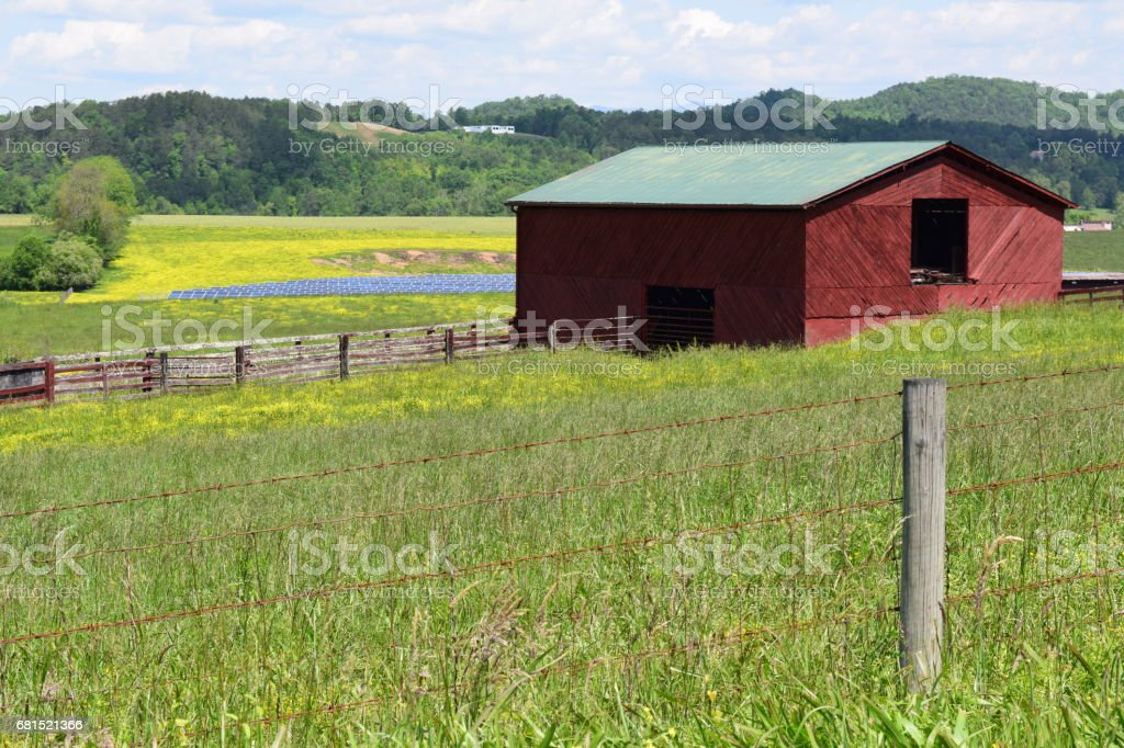 Red barn surrounded by fenced fields stock photo