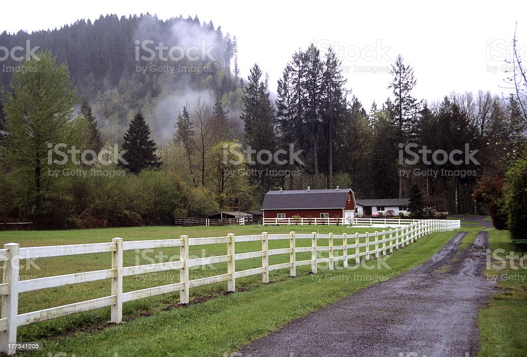 Red barn with white fence on misty day stock photo