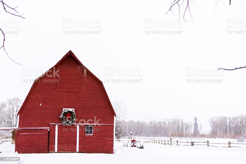 Red barn with white snow and sky stock photo