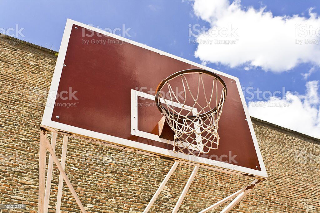 Red basketball board over brick wall and blue sky royalty-free stock photo