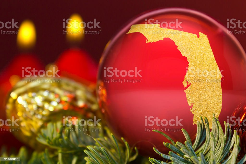 Red bauble with the golden shape of Florida.(series) stock photo