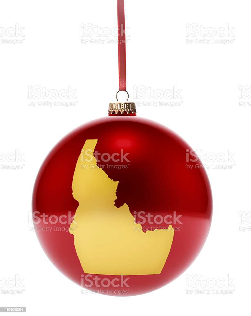 Red bauble with the golden shape of Idaho.(series) stock photo