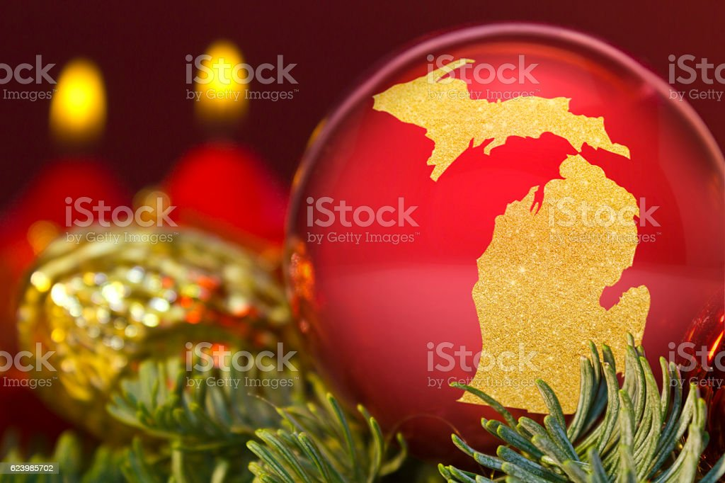 Red bauble with the golden shape of Michigan.(series) stock photo