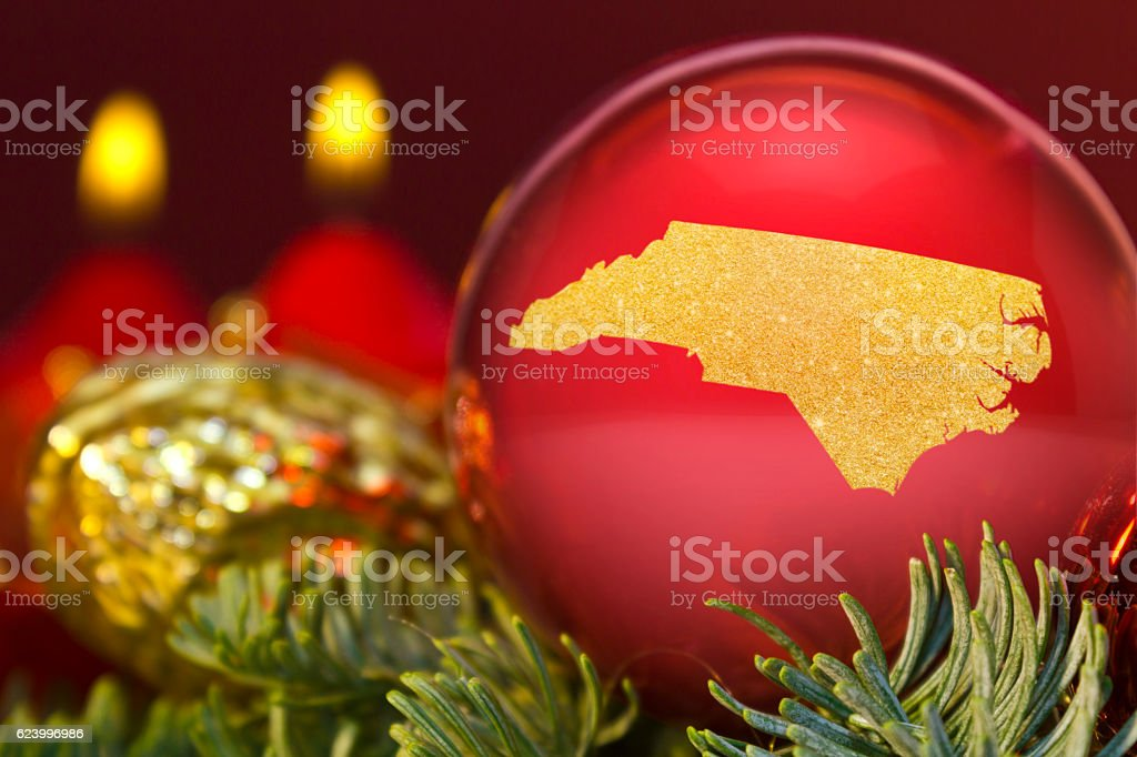 Red bauble with the golden shape of North Carolina.(series) stock photo