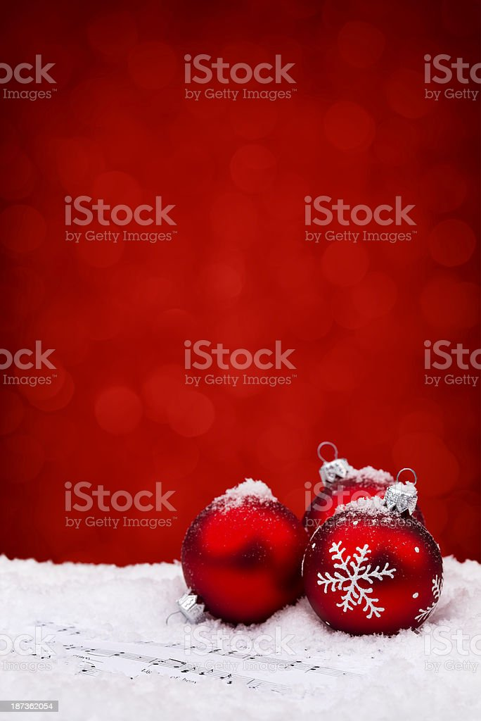 Red baubles on sheet notes with christmas carols and snow royalty-free stock photo