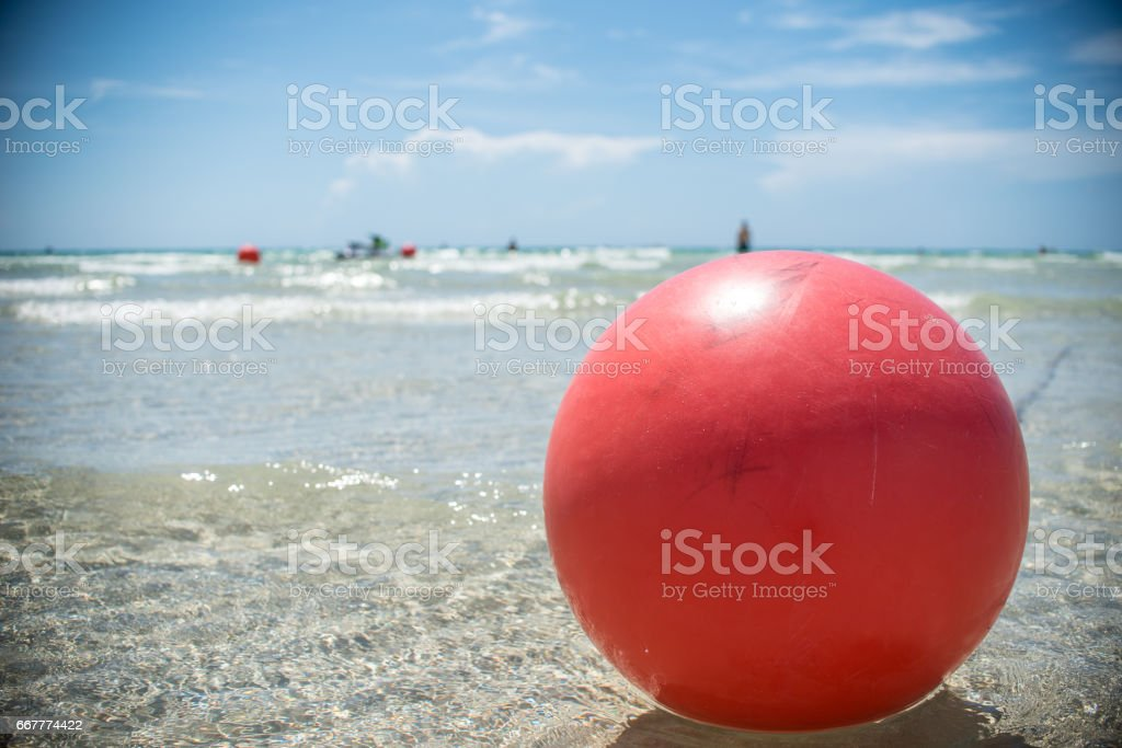 red beach ball in ocean stock photo