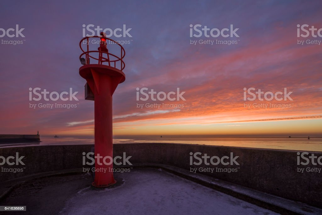 Red beacon on jetty under romantic sky stock photo