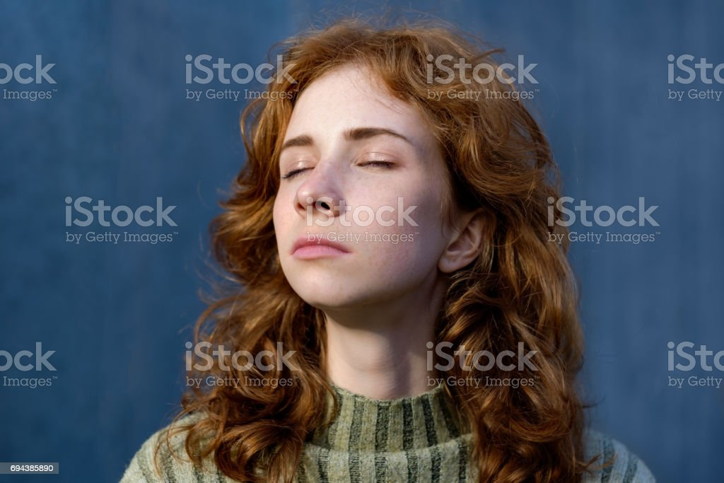 A red, beautiful girl with freckles closes her eyes and looks away. stock photo