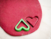 Red beet dough with a heart cut out cookies