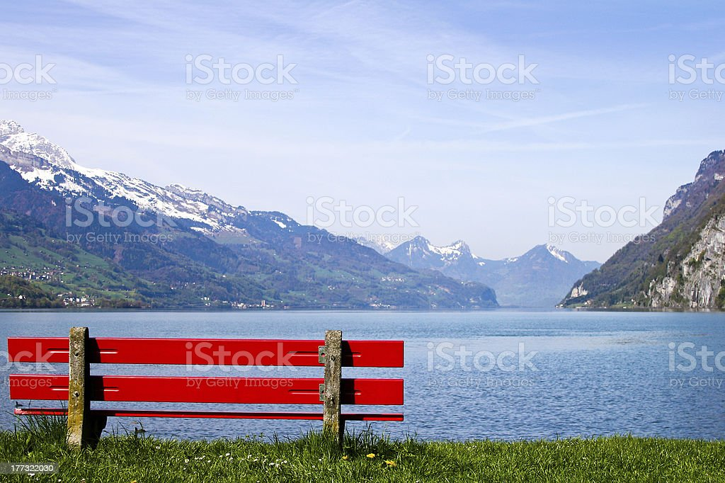 Red bench in front of the lake stock photo