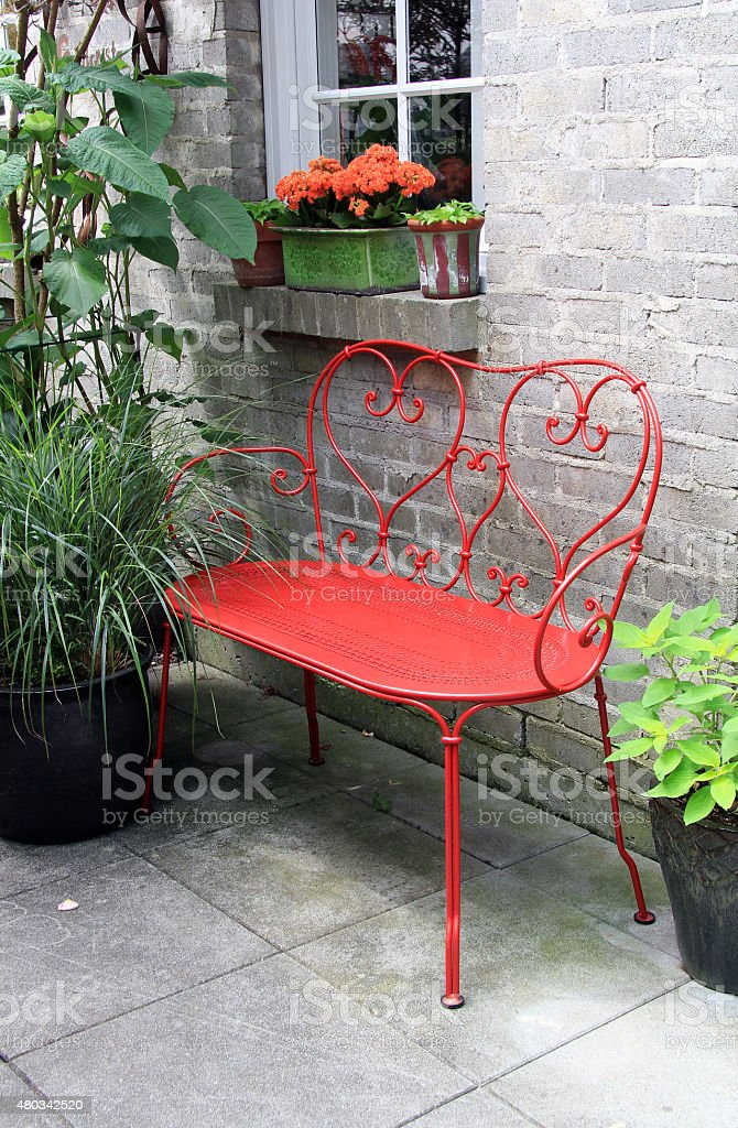 Red bench outside on a patio stock photo