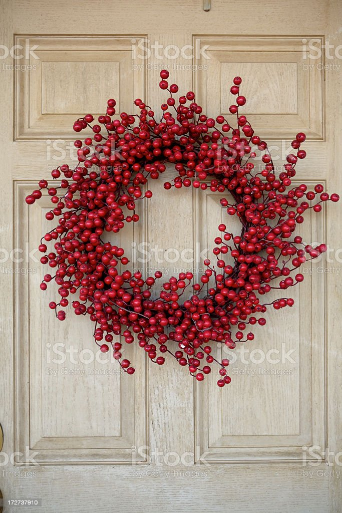 Red berry wreath against an ivory colored door  royalty-free stock photo