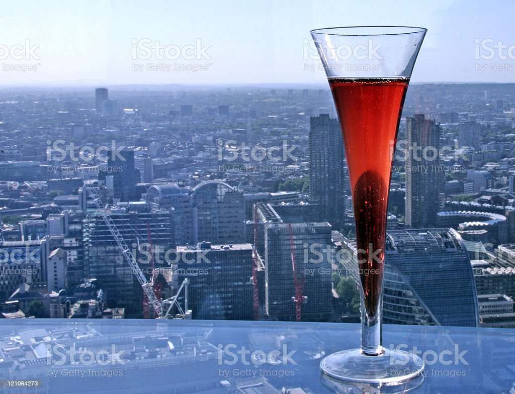 A red beverage resting on a balcony overlooking a cityscape royalty-free stock photo