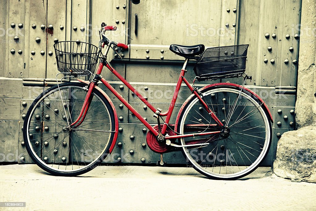 Red Bicycle Leaning Against Wall on Italian Street stock photo