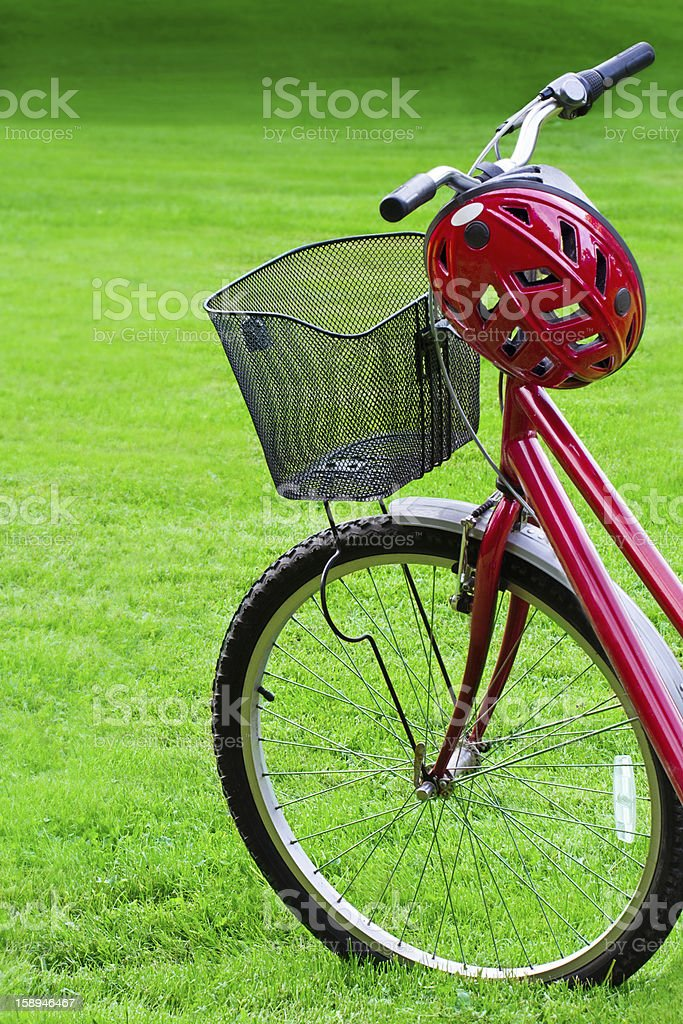 Red bike and a helmet on green grass royalty-free stock photo