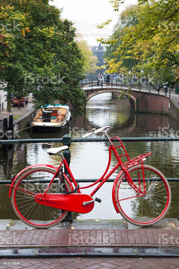 Red bike on a bridge in Amsterdam stock photo