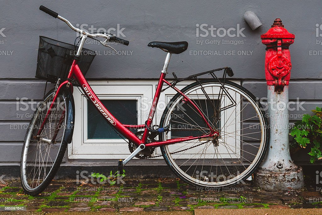 Red Bike with Bucket near Fire Pump stock photo